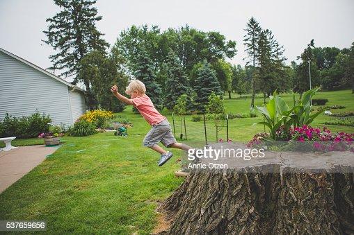 Boy Jumping off of stump
