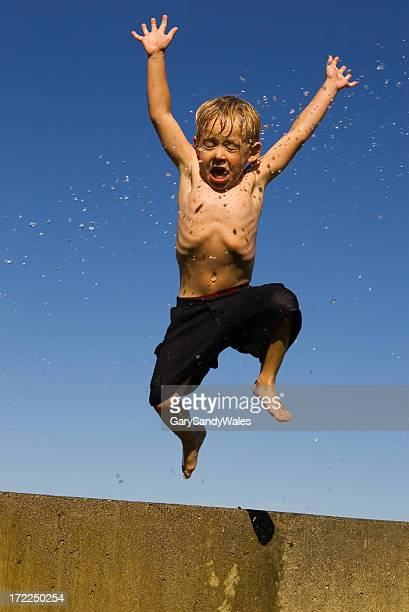 Boy jumping off wall