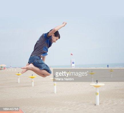 Boy jumping on a beach : Stock Photo