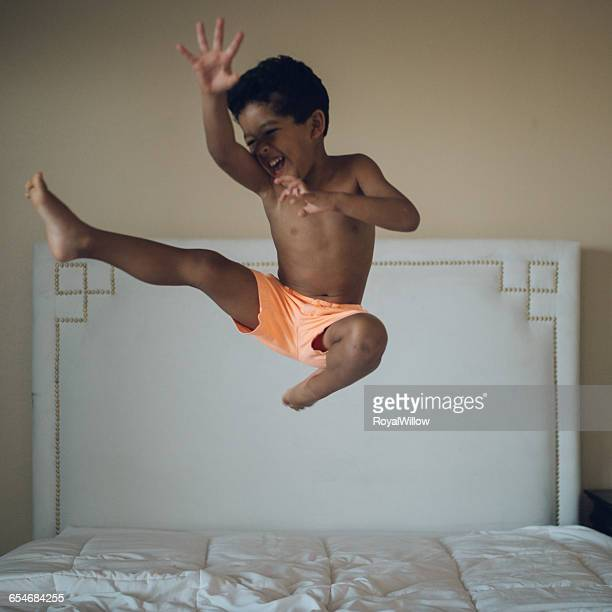 Boy jumping on bed in bedroom