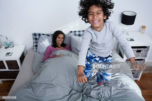 Boy jumping on bed, mother watching smiling