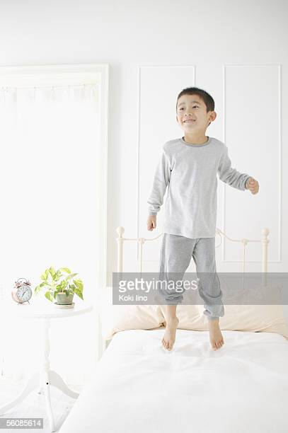 A boy jumping on bed