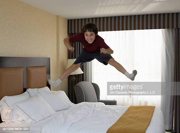 Boy (10-11) jumping on bed
