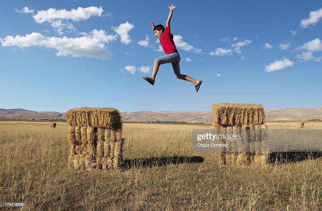 Boy jumping on hay bales