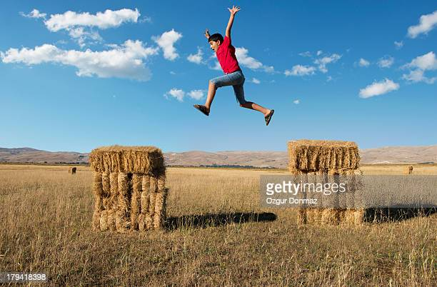 Boy jumping on hay bales
