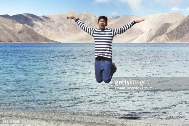 Boy Jumping On Lakeshore Against Mountains