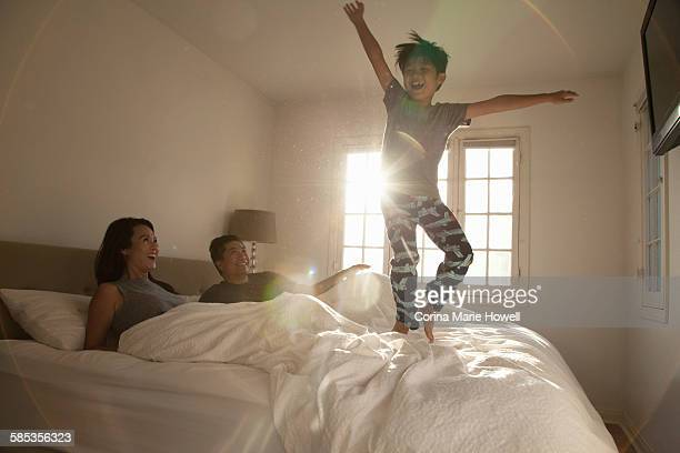 Boy jumping on parents bed