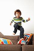 Boy jumping on sofa
