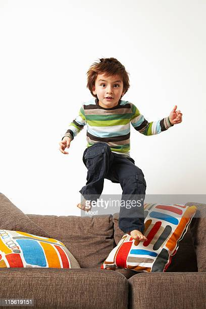 Boy jumping on sofa