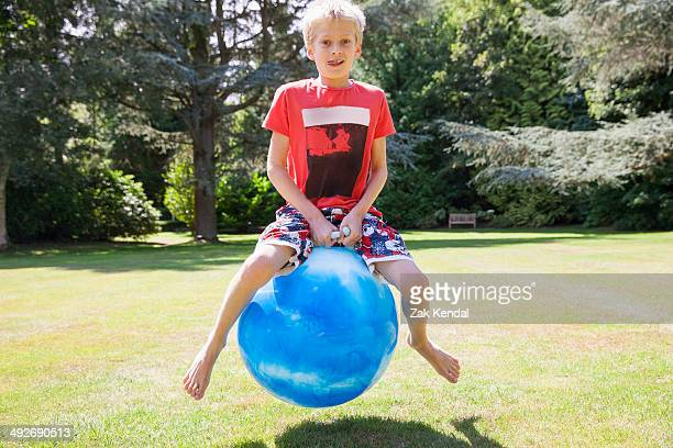 Boy jumping on space hopper