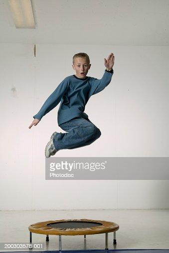 Boy (8-9), jumping on trampoline in studio, portrait