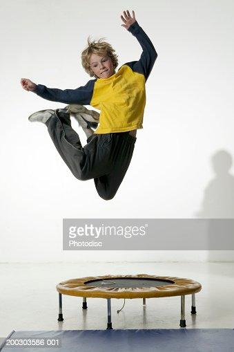 Boy (12-13), jumping on trampoline in studio, portrait
