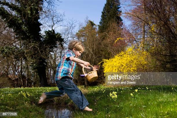 boy jumping over creek holding basket