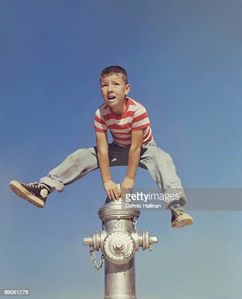 Boy jumping over fire hydrant