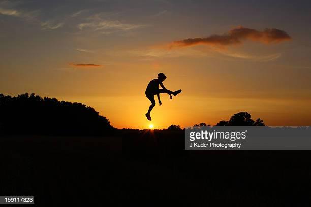 Boy jumping over sun