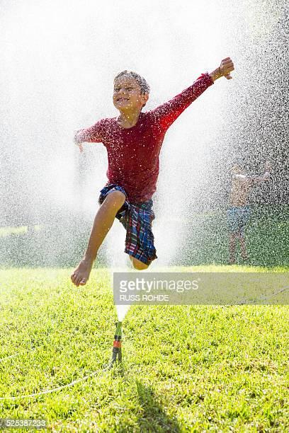 Boy jumping over water sprinkler in garden