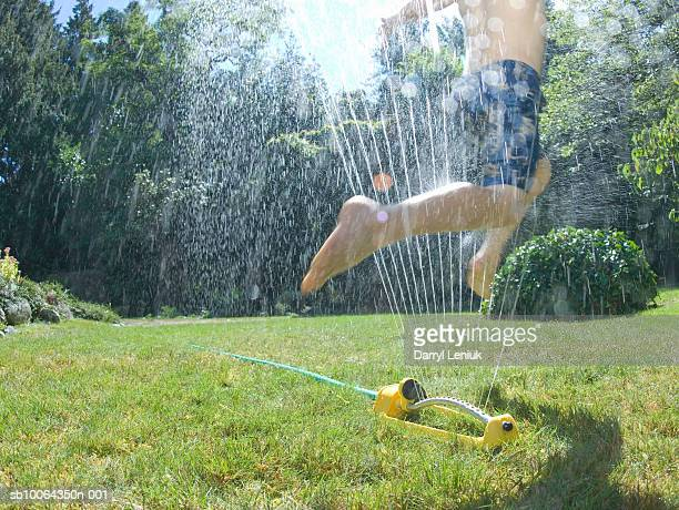 Boy (6-7) jumping through water sprinkler