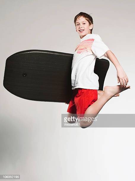 Boy (12-13)  jumping with boogie board, smiling, portrait