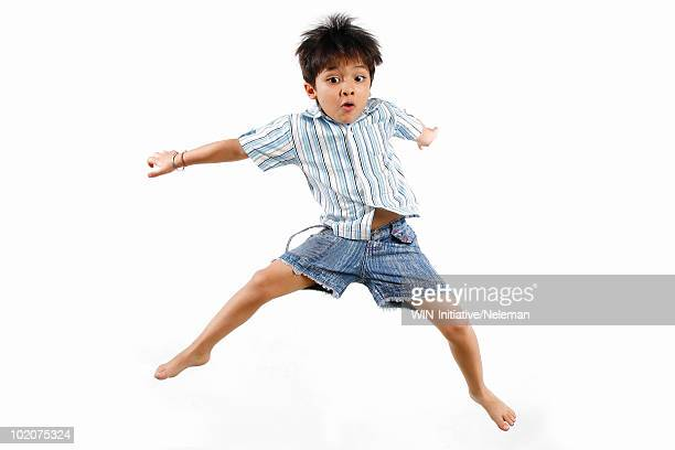 Boy jumping with his legs apart