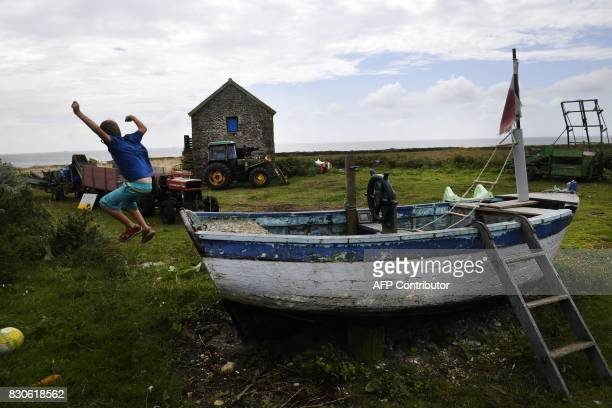 A boy jumps from a boat in a garden near a farm in the island of Quemenes in Le Conquet western France on August 9 2017 A family rehabilated a...