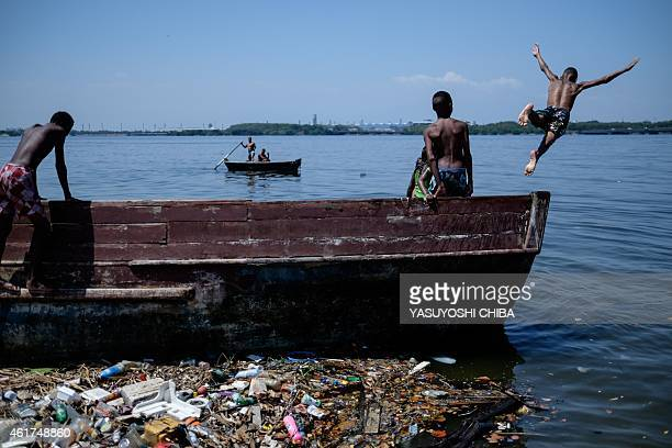 A boy jumps from a boat into polluted water of Guanabara bay in Rio de Janeiro Brazil on January 18 2015 AFP PHOTO / YASUYOSHI CHIBA