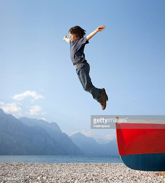 Boy jumps from a boat