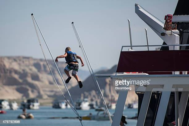 A boy jumps from the top of his houseboat at the Wahweap Marina on Lake Powell in Page Arizona US on Thursday June 25 2015 Due to severe drought Lake...