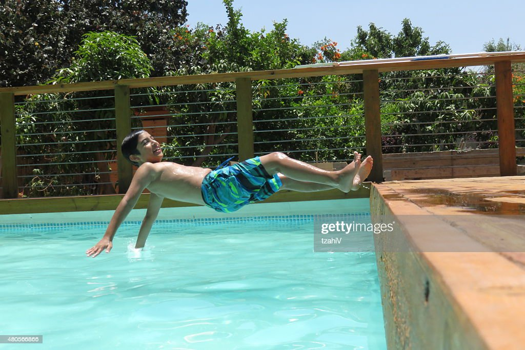 boy jumps into blue water : Stock Photo
