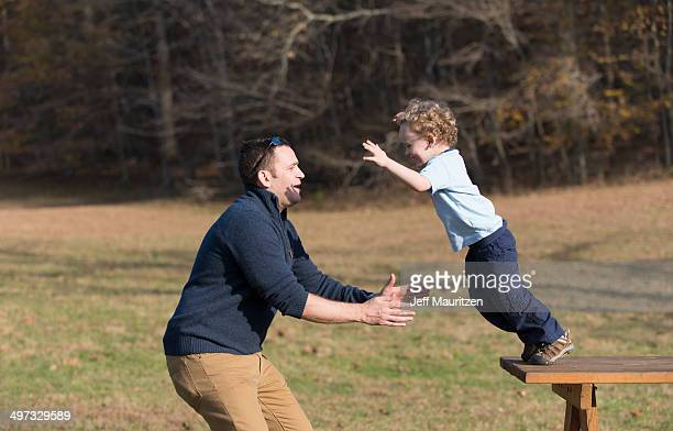 A boy jumps into his father's arms.