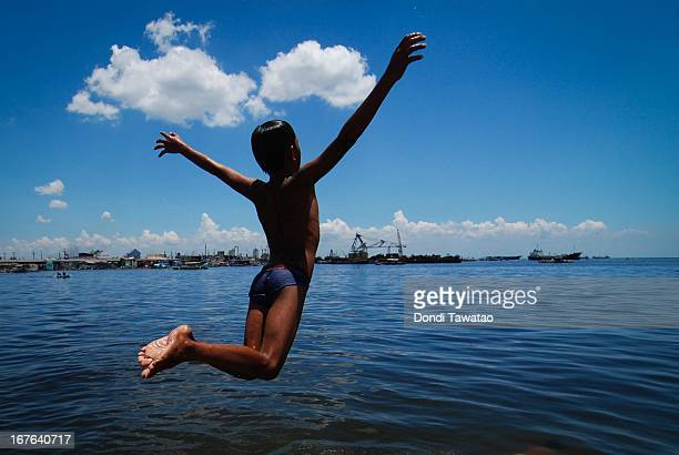 A boy jumps into the murky waters of Navotas de Bay on April 27 2013 in Manila Philippines Despite small rainshowers temperatures soared from 35 to...