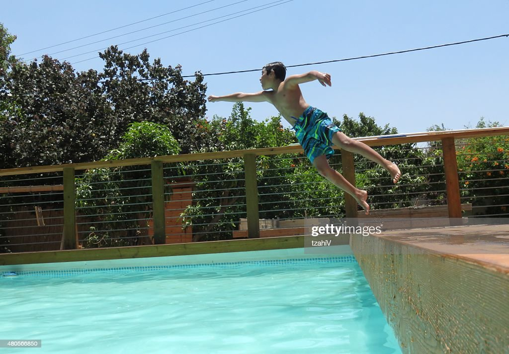 Boy jumps into the pool : Stock Photo