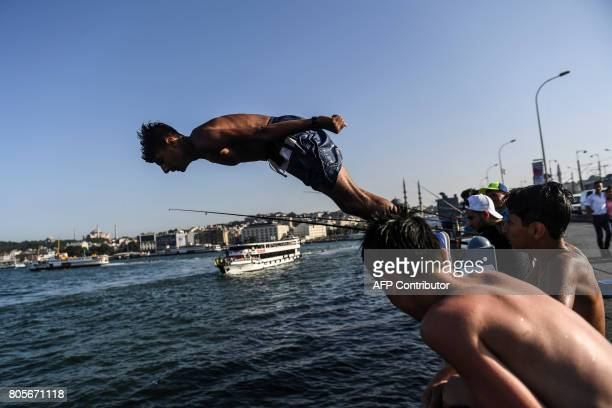 A boy jumps into the sea from the Galata bridge on July 2 in Istanbul Turkey was sweltering in a weekend heatwave that caused record temperatures in...