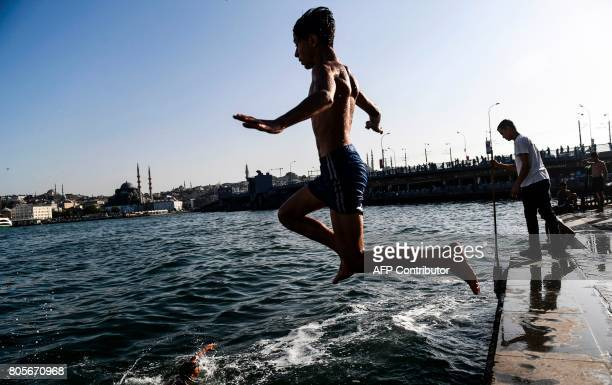 A boy jumps into the sea from the Karakoy port on July 2 in Istanbul Turkey was sweltering in a weekend heatwave that caused record temperatures in...
