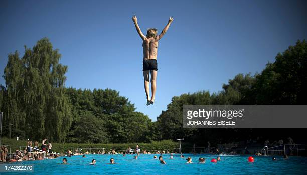 A boy jumps into the water of a public swimming pool on July 23 2013 in Berlin's Neukoelln district as temperatures in the capital reached 30 degrees...