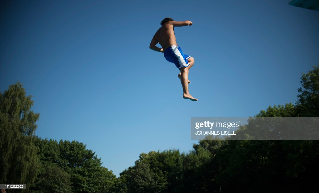 A boy jumps into the water of a public swimming pool on July 23, 2013 in Berlin's Neukoelln district as temperatures in the capital reached 30 degrees Celsius. AFP PHOTO / JOHANNES EISELE