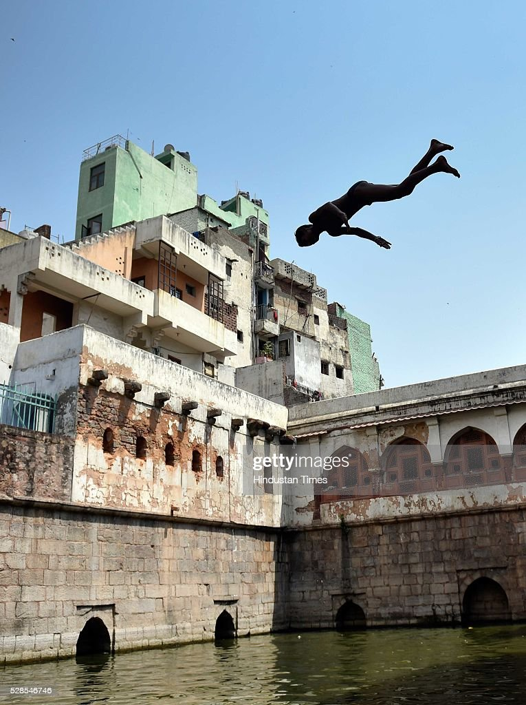 A boy jumps into the water of baoli during a hot sunny day at the Nizamuddin Dargah, on May 5, 2016 in New Delhi, India. The national capital sizzling today as heat wave-like conditions prevailed across the city with mercury hovering above 40 degree Celsius, making life tough for the Delhiites.