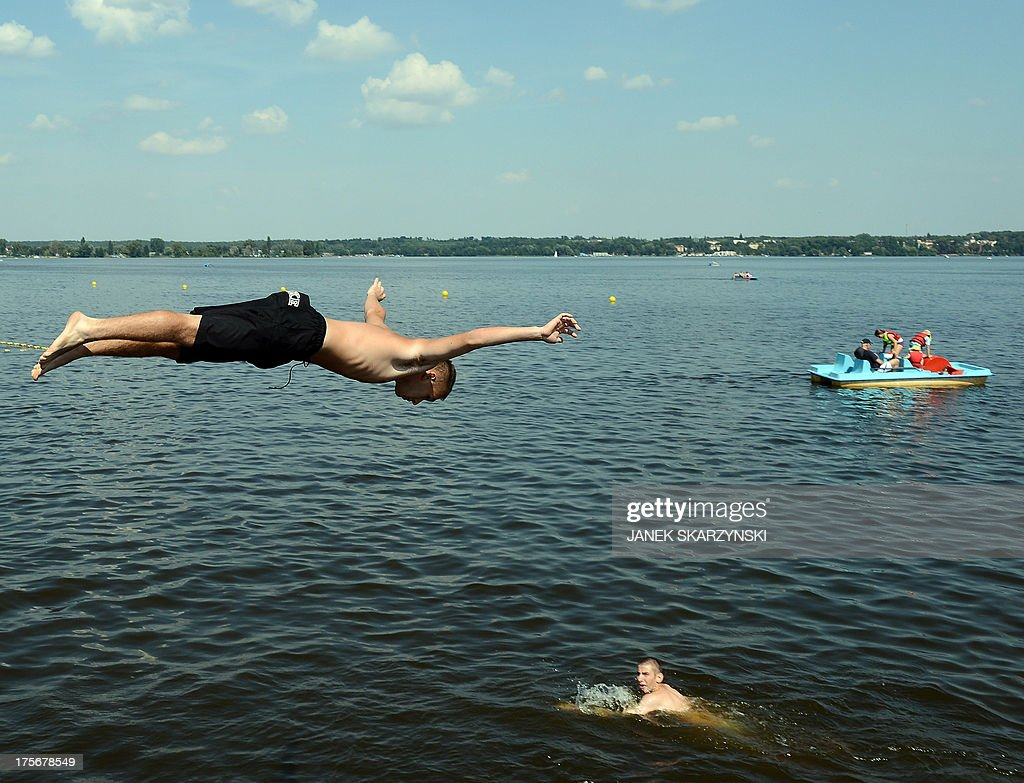 A boy jumps into Zegrze lake near Warsaw, Poland on August 6, 2013. Thirty-five people have drowned in Poland since the beginning of August, according to police, as Poles attempt to combat a heatwave by flocking to the beach.