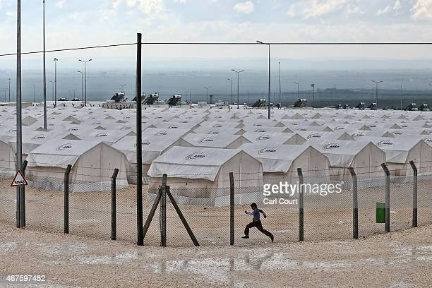 A boy jumps over a puddle in Suruc refugee camp on March 25 2015 in Suruc Turkey The camp is the largest of its kind in Turkey with a population of...