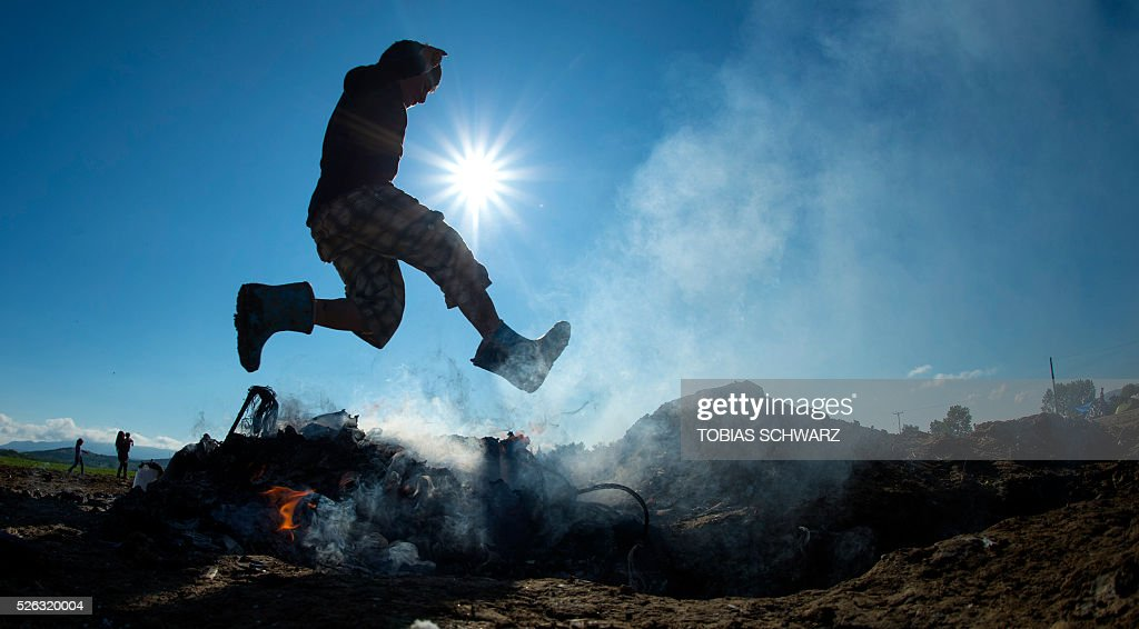 A boy jumps over burning rubbish a makeshift camp for migrants and refugees near the village of Idomeni, not far from the Greek-Macedonian border, on April 30, 2016. Some 54,000 people, many of them fleeing the war in Syria, have been stranded on Greek territory since the closure of the migrant route through the Balkans in February. / AFP / TOBIAS