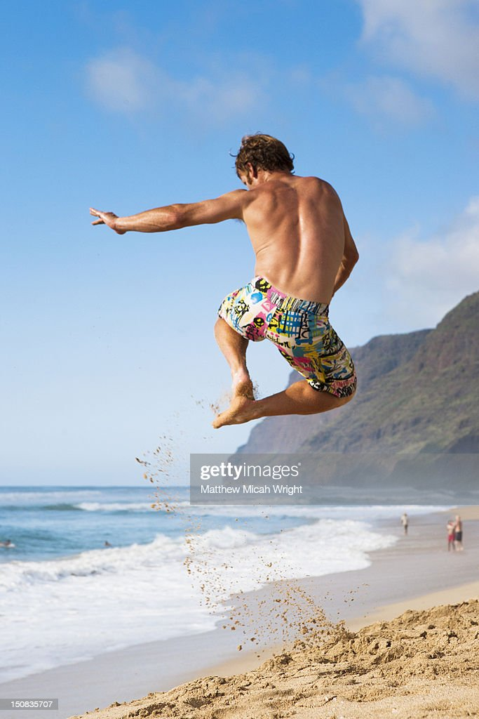 A boy jumps through the air at the beach. : Stock Photo