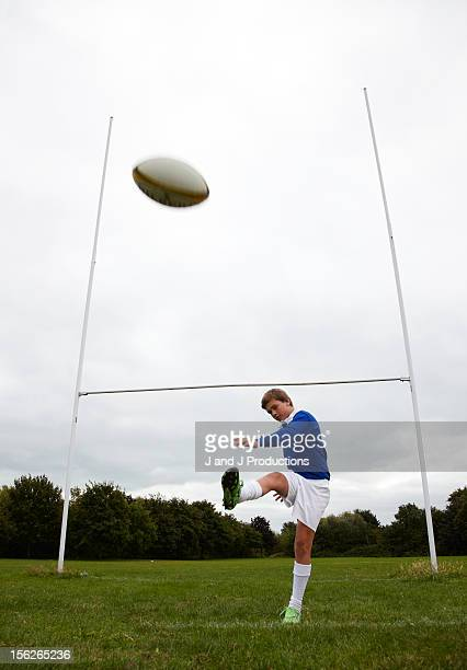 Boy kicking a rugby ball