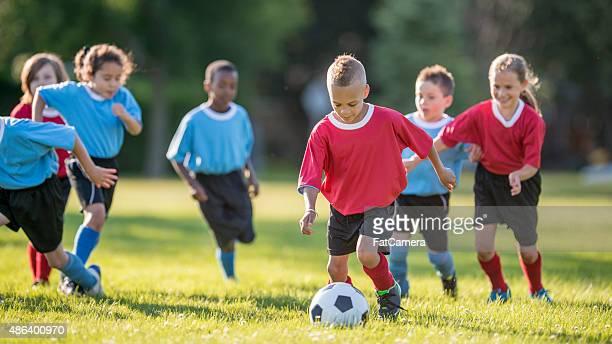 Garçon taper dans un ballon de football