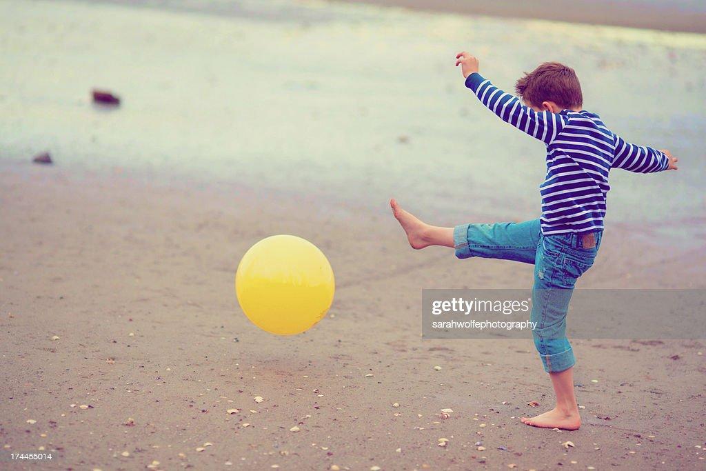 boy kicking ball on beach