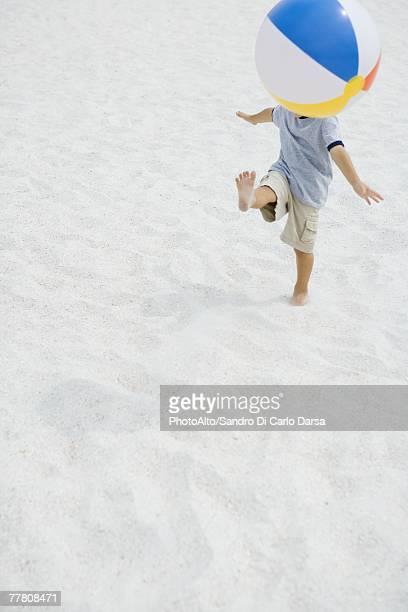 Boy kicking beach ball on beach, head hidden by ball, high angle view, full length