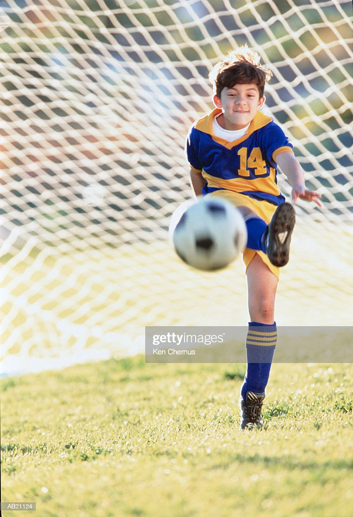 Boy (5-7) kicking football, goal net in background : Stock Photo