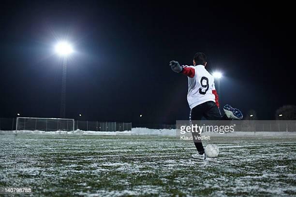 Boy kicking football (soccer) towards goal