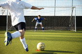 Boy (9-11) kicking soccer ball at goal, rear view
