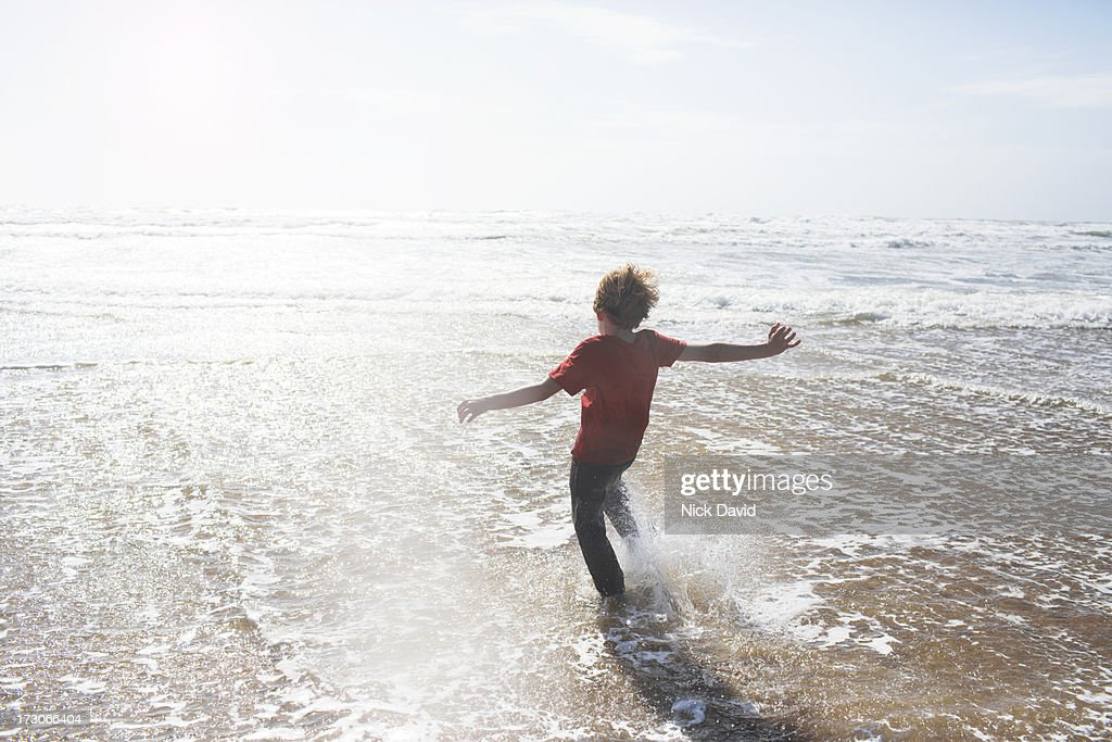 boy kicking water at the seaside : Stock Photo