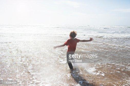 boy kicking water at the seaside : Bildbanksbilder