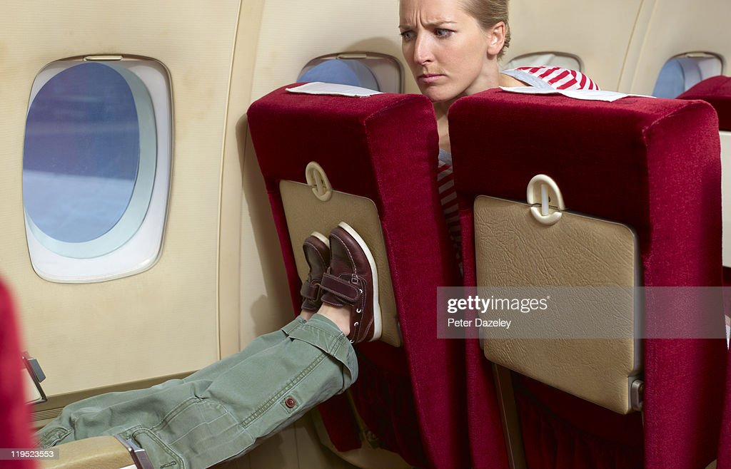 Boy kicking woman's seat on plane : Stock Photo